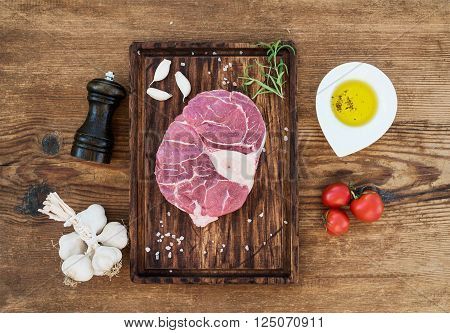 Raw fresh beef meat cross cut for ossobuco cut with garlic cloves, cherry tomatoes, rosemary, pepper, oil and salt on serving board over rustic wooden background, top view