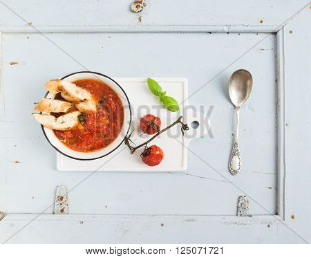 Italian tomato, garlic and basil soup Pappa al Pomodoro in metal bowl with bread white ceramic serving board over light blue background, top view