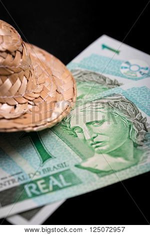 brasil money on a black background with a straw hat concept holiday