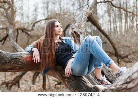 Young Hipster Girl With Long Hair And A Denim Jacket Lying On A Tree