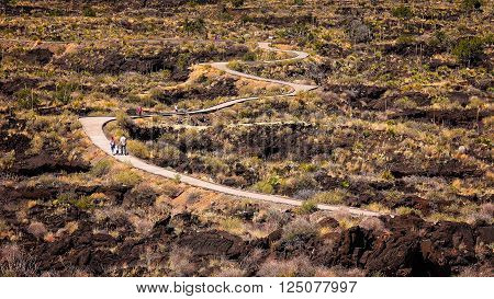 Visitors on the curved walkway through lava fields at Valley of Fires Recreation Area in New Mexico