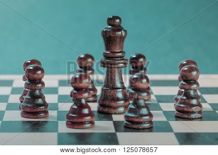 Chess team and teamwork concept with wooden chess pieces and chess queen. Photography with blue background. ** Note: Shallow depth of field