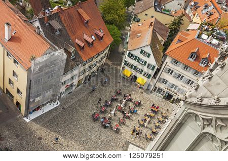 People Sitting At Outdoors Cafe In Old Town Of Konstanz, Germany