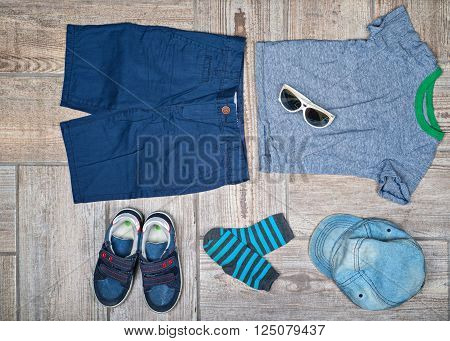 Flat lay photography of boy's casual outfit. Boy's outfit on wood board background