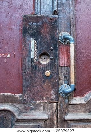 Old wooden door with flat buttons and vintage handle