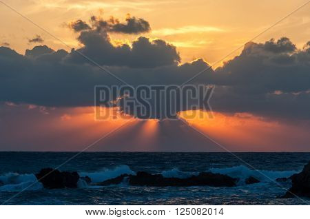 sunset at the Mediterranean sea. slanting rays breaking through the clouds