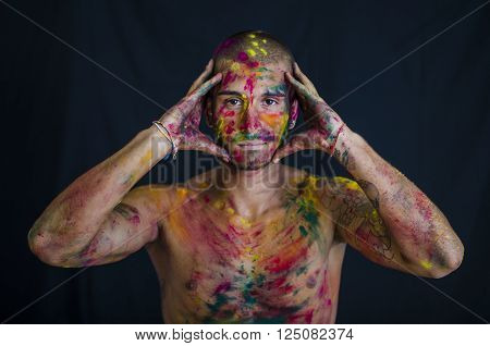 Head and shoulders shot of attractive young man shirtless, skin painted all over with bright Holi colors, looking at camera, isolated on white background ** Note: Soft Focus at 100%, best at smaller sizes