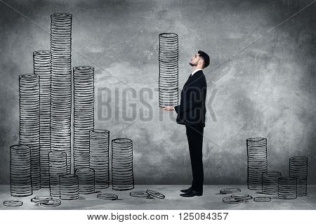 Just making money. Full length of confident young man in full suit carrying illustrated coin stack while standing against concrete wall