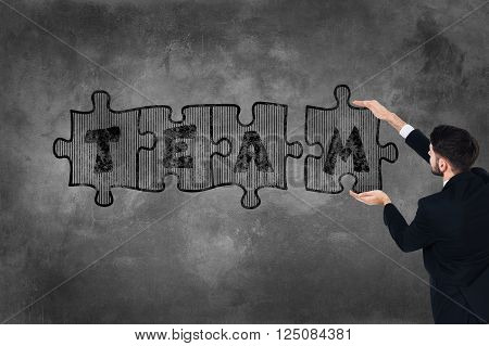 Be the team! Rear view of young man in full suit touching concrete wall with illustrated puzzle on it