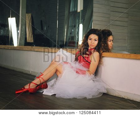 Beautiful woman ballet dancer resting after the performance in a rehearsal, dressed in red pointe shoes, skirt and red corset