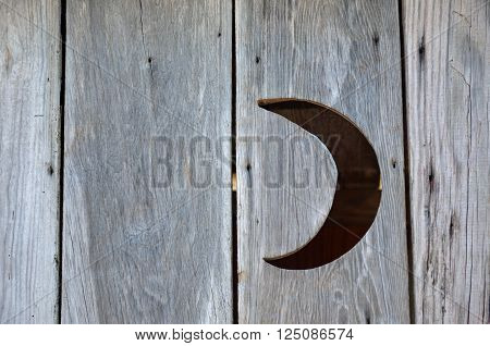 A cutout of a crescent moon in an aging  wooden outhouse structure