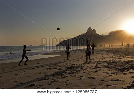 RIO DE JANEIRO, BRAZIL - APRIL 8: Silhouettes of locals playing beach football on the shore of Ipanema Beach wit Two Brothers Mountain on the Background on April 8, 2016, Rio de Janeiro, Brazil