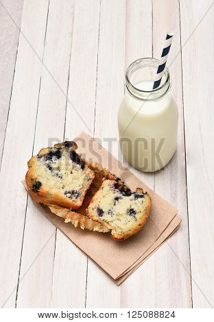 High angle view of a blueberry muffin and bottle of milk on a rustic white table. The muffin is broken in half on a napkin. Vertical format.