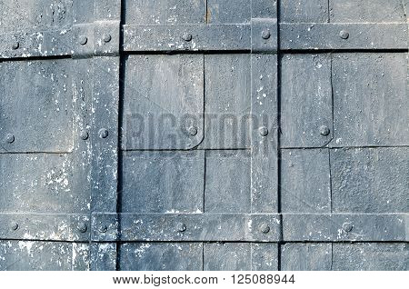 Textured metal background with grunge superficies - grey painted hammered metal plates with rivets and stripes above