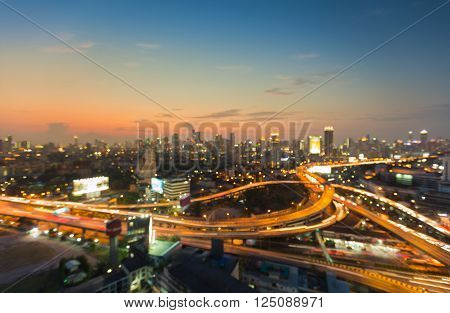 Aerial view burred light city interchanged road and office building background during sunset