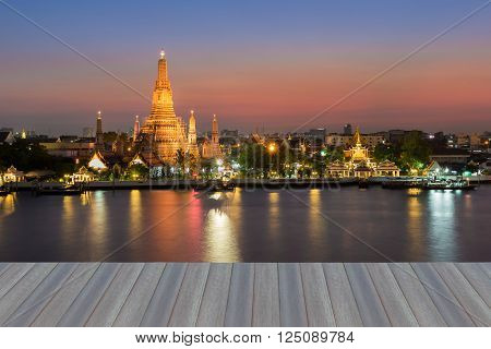 Opening wooden floor, Twilight of Arun temple water front, the most famous landmark of Thailand