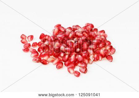 Juicy pomegranate fruit seeds, on white background.