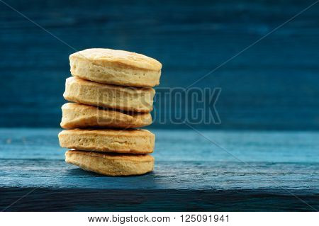 Pile of tasty round imperfect homemade cookies on deep blue background