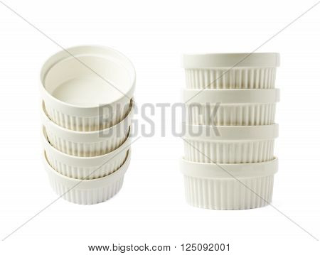 Pile of multiple white porcelain souffle ramekin dishes isolated over the white background, set of two different foreshortenings