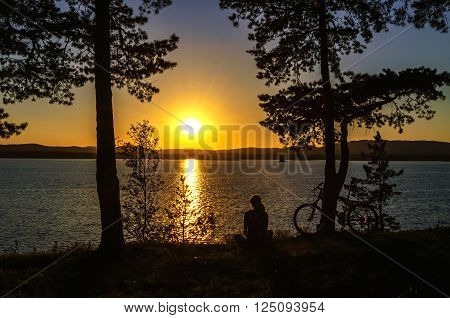 Summer silhouette landscape - unidentified tourist girl sitting at the edge of the cliff and looking the sun setting behind the mountains on Irtyash Lake in Southern Urals Russia