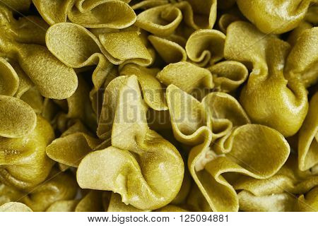 Surface covered with sacchettoni green stuffed sacchetti pasta, close-up fragment crop as a background composition