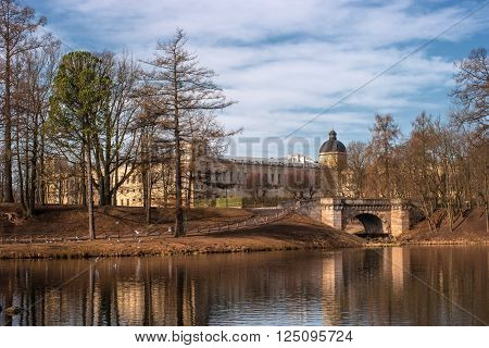 Gatchina Palace. View of the Palace and Karpin bridge from the White Lake.  Palace reflected in the water. Strict and grand palace.