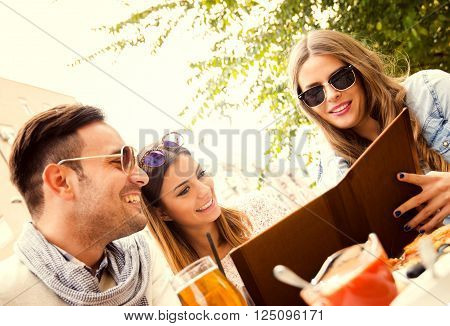 Young group of laughing people eating pizza and having fun.They are enjoying eating and drinking together.