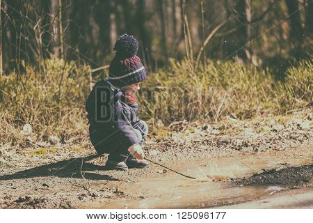 Little Boy Playing In Puddle In Spring