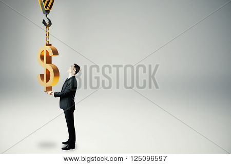 Investment concept with businessman holding golden dollar sign suspended on crane hook. 3D Rendering