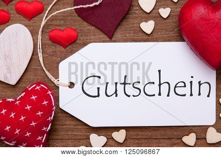 Label With Red Textile Hearts On Wooden Gray Background. German Text Gutschein Means Voucher. Retro Or Vintage Style. Macro Or Close Up Of One Label
