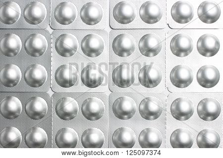 Background of round pills in silvery blisters