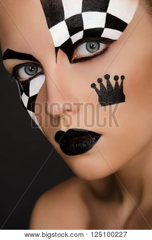 beautiful woman with black and white face art on black background