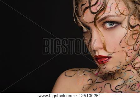 woman with wet hair and face art on black background