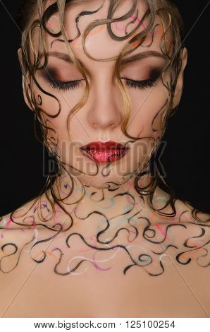 portrait of beautiful woman with wet hair and face art on black background