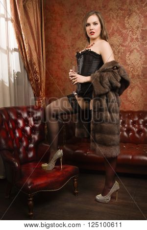 Sexy Brunette Young Woman Wearing Black Lingerie, Fur Cape And Stockings With A Glass Of Champagne
