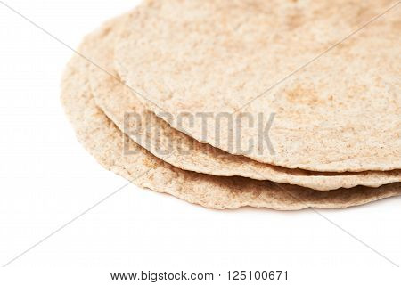 Pile of wheat tortillas isolated over the white background, close-up crop fragment as a copyspace backdrop composition