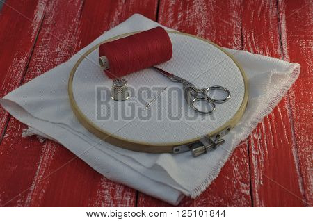 The fabric in the hoop for the embroidery with a reel of red thread