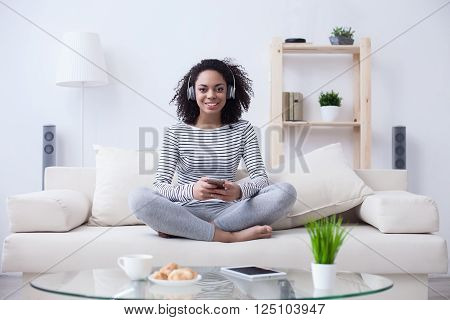 Cheerful young african girl is listening to music at home. She is sitting on sofa and holding a mobile phone. The lady is wearing headphones. She is smiling