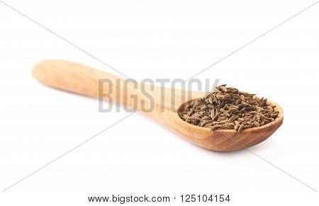 Wooden spoon full of cumin seeds isolated over the white background