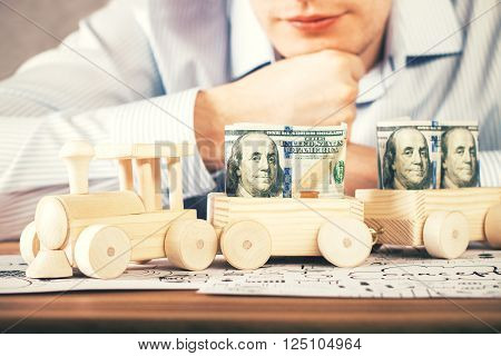 Caucasian businessman looking at wooden toy train filled with dollar banknotes