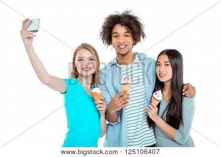 Studio shot of nice young multicultural friends. Beautiful people looking at camera, smiling, making selfie photo on mobile phone and holding ice-creams. Isolated background