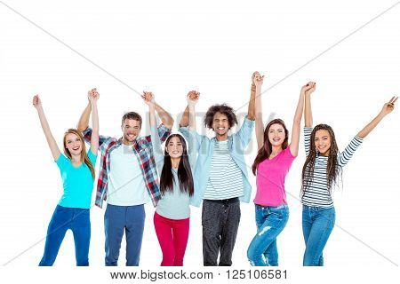 Studio shot of nice young multicultural friends. Beautiful people looking at camera, holding hands up and cheerfully smiling. Isolated background