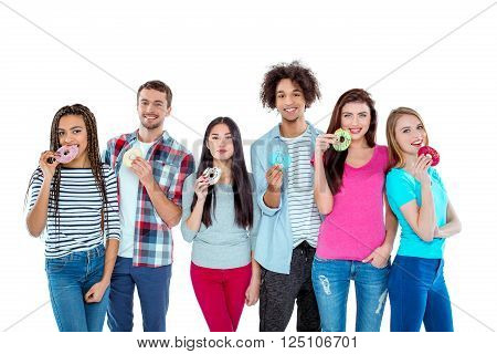Studio shot of nice young multicultural friends. Beautiful people with sweet donuts looking at camera and smiling. Isolated background
