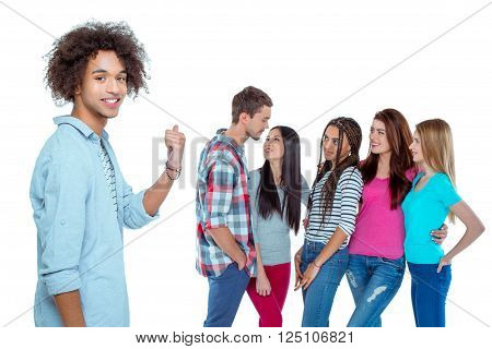 Studio shot of nice young multicultural friends. Beautiful people chatting. Focus on african boy. He looking at camera, pointing at friends and smiling. Isolated background