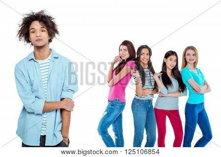 Studio shot of nice young multicultural people. Beautiful girls chatting and looking at young man. Focus on african boy. He looking at camera. Isolated background