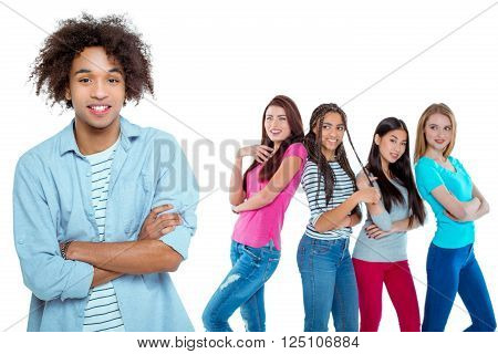 Studio shot of nice young multicultural people. Beautiful girls chatting and looking at young man. Focus on african boy. He looking at camera and smiling. Isolated background