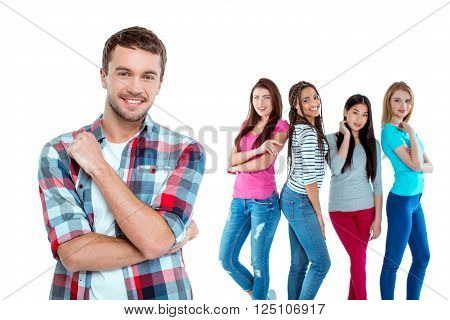 Studio shot of nice young multicultural people. Beautiful girls chatting and looking at young man. Focus on boy. He looking at camera and smiling. Isolated background