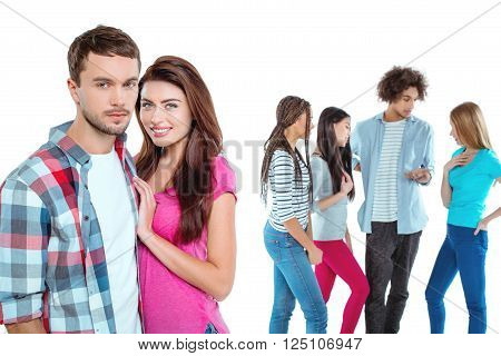 Studio shot of nice young multicultural friends. Beautiful people chatting. Focus on young couple. Couple looking at camera and smiling. Isolated background