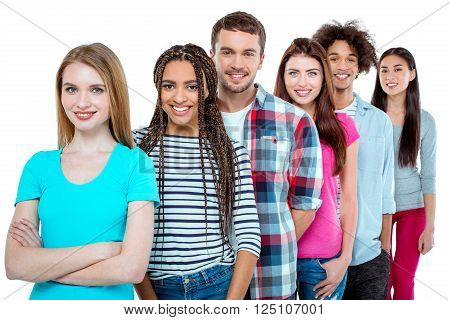 Studio shot of nice young multicultural friends. Beautiful people standing in a row, looking at camera and smiling. Isolated background