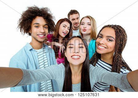 Studio shot of nice young multicultural friends. Beautiful people cheerfully smiling and having fun while making selfie photo. Isolated background